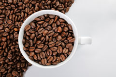 A cup of coffee beans on the edge of diagonal coffee beans shape Stock Photo