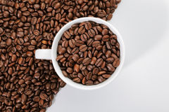 A cup of coffee beans on the edge of diagonal coffee beans shape Royalty Free Stock Photos