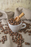 Cup of coffee beans on fabric on grey background Stock Photo