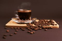 Cup of coffee with beans. Cup of coffee with foam, with coffee beans, lying on the wooden stand, on brown background Royalty Free Stock Image
