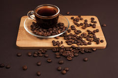 Cup of coffee with beans. Cup of coffee with foam, with coffee beans, lying on the wooden stand, on brown background Royalty Free Stock Photo