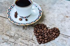 Cup of coffee and beans in form of heart Stock Photos