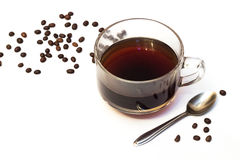Cup of coffee and beans. Cup of coffee and grains scattered on a table and a spoon on a white background Royalty Free Stock Image