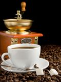 Cup of coffee, beans and grinder Royalty Free Stock Images