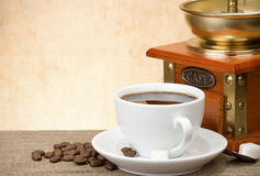 Cup of coffee with beans and grinder Stock Photo