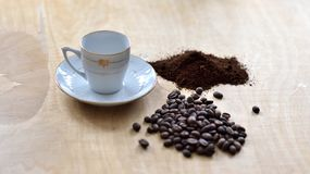 Cup with coffee beans and grounded coffee stock photo