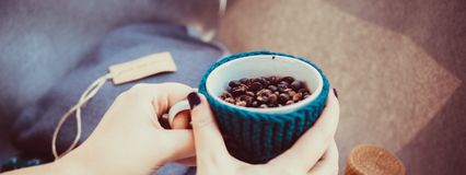 Cup of coffee beans, hands and warm woolen sweater, decorated with led lights, top view point. stock photo