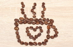 Cup of coffee beans with heart shape. Wooden background Stock Photography