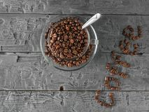 A Cup of coffee beans and coffee inscription on a wooden table. The view from the top. Grains for the preparation of the popular royalty free stock images