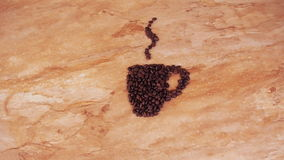A cup of coffee beans. On the kitchen marble table a sign of a cup of coffee beans. stock footage