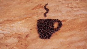 A cup of coffee beans. On the kitchen marble table a sign of a cup of coffee beans. stock video
