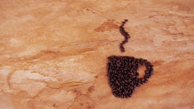 A cup of coffee beans. On the kitchen marble table a sign of a cup of coffee beans stock footage