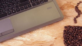 A cup of coffee beans with a laptop. On a kitchen marble table a sign of a cup of coffee beans and a laptop. stock video