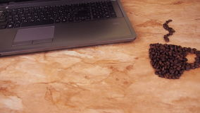 A cup of coffee beans with a laptop. On a kitchen marble table a sign of a cup of coffee beans and a laptop. stock footage