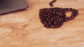 A cup of coffee beans with a laptop. On a kitchen marble table a sign of a cup of coffee beans and a laptop stock video