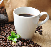 Cup of coffee with beans and leaf. Stock Photos