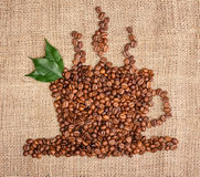 Cup of coffee from beans with leaves Royalty Free Stock Photos