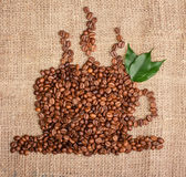 Cup of coffee from beans with leaves on sackcloth background Royalty Free Stock Photos