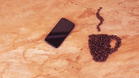 A cup of coffee beans and a mobile phone. On the kitchen marble table the sign of a cup of coffee beans and mobile. stock footage