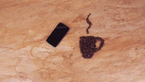 A cup of coffee beans and a mobile phone. On the kitchen marble table the sign of a cup of coffee beans and mobile. stock video