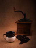 Cup of coffee with beans and an old grinder on the background Stock Image
