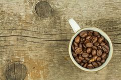 Cup of coffee beans on old wooden table. Sales of coffee. Decorations for the menu. Coffee shop. Stock Photo