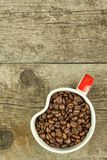 Cup of coffee beans on old wooden table. Sales of coffee. Decorations for the menu. Coffee shop. Stock Photos