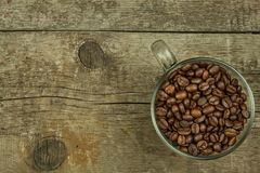 Cup of coffee beans on old wooden table. Sales of coffee. Decorations for the menu. Coffee shop. Stock Photography