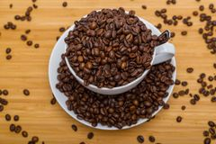 Cup of coffee beans overflowing royalty free stock image