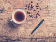 Cup of coffee with beans and a pen Royalty Free Stock Images