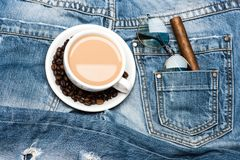 Cup with coffee and beans on plate on denim background. Modern culture of drinking coffee, top view. Mug full of coffee Stock Images