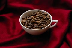 Cup with coffee beans on a red plaid. White cup with coffee beans on a red plaid Stock Image
