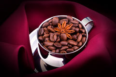 Cup of Coffee with beans on red silk Royalty Free Stock Photography