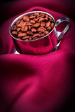Cup of Coffee with beans on red silk Stock Images