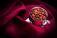 Cup of Coffee with beans on red silk Stock Photo