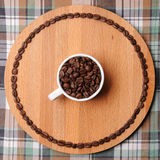 Cup with coffee beans on round wooden board with circuit of the coffee beans. On plaid background. White cup with coffee beans on round wooden cutboard with royalty free stock photography