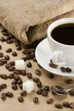 Cup of coffee and beans at sacking Stock Photography