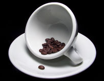 Cup of coffee beans on saucer. Color photo of a tilted white coffee cup with a handful of dark brown coffee beans on a matching white saucer.  One coffee bean Stock Image
