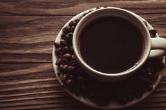 Cup of coffee, coffee beans on saucer on wooden background royalty free stock photos