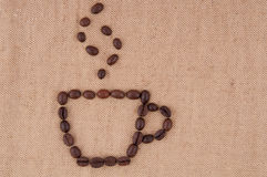A cup of coffee beans with smoke. A cup of coffee beans with smoke on the background of burlap Stock Photo