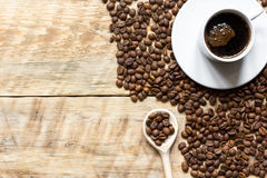 Cup of coffee, beans and spoon on wooden background Royalty Free Stock Photos