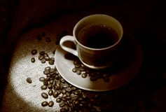 Cup of coffee with coffee beans standing on a sacking Royalty Free Stock Photography