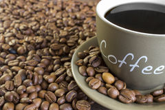 Cup of coffee  with beans standing on a wooden table. Royalty Free Stock Photo