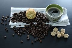 Cup of coffee with beans, sugar and newspaper. Coffee beans and sugar near a cup of coffee and a newspaper, black background, copyspace stock photos