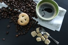 Cup of coffee with beans, sugar and newspaper. Coffee beans and sugar near a cup of coffee and a newspaper, black background, copyspace royalty free stock images