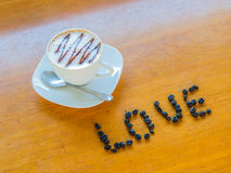 Cup of coffee with  beans. A cup of coffee with  beans to shape LOVE Royalty Free Stock Photography