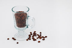 Cup with coffee beans. Transparent cup with coffee beans on white background.coffee beans are about cup Stock Photos