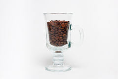Cup with coffee beans. Transparent cup with coffee beans on white background Royalty Free Stock Photo