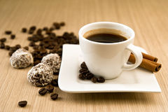 Cup of coffee with beans and truffles Royalty Free Stock Image