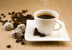 Cup of coffee with beans and truffles Stock Photos